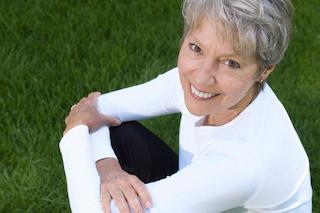 a woman smiles while sitting in grass | hartford ct fixed dental bridges
